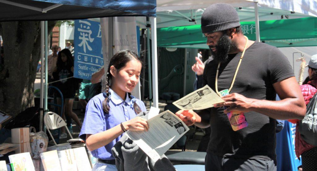 鄭心謙(左)是華盛頓大學一年級新生,在慈濟攤位前面解說素食食譜。