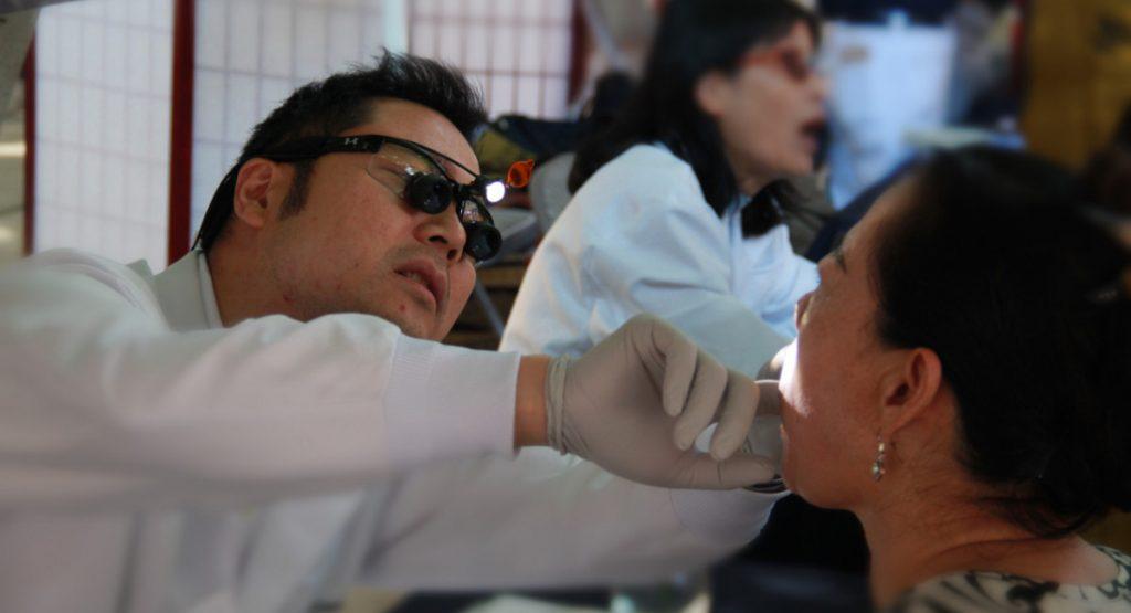 江捷豪醫生(左)細心的為民眾檢查口腔與牙齒並提供建議。攝影/張立甲