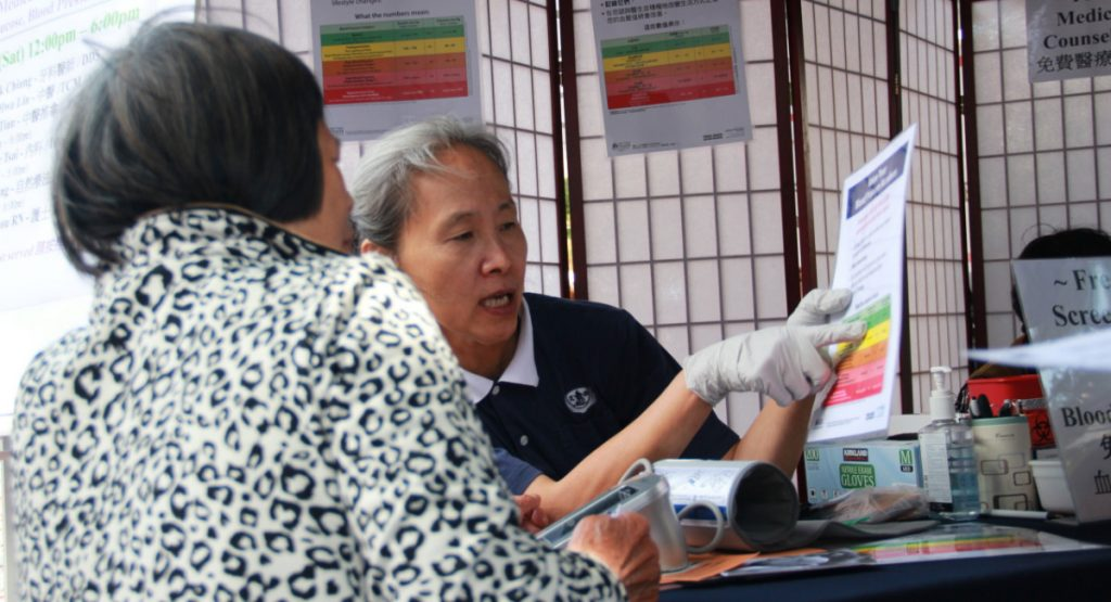 志工陳盈伶(右)向民眾說明如何控制血壓。攝影/應仲銘