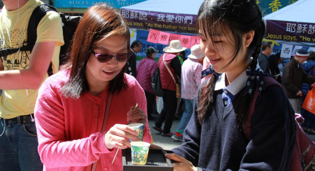 慈青曾藝琳(右)向民眾奉茶。攝影/張立甲