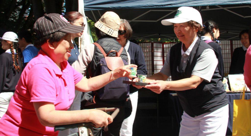 志工胡招鳳(右)奉茶時,總是堆滿了笑容。攝影/張立甲