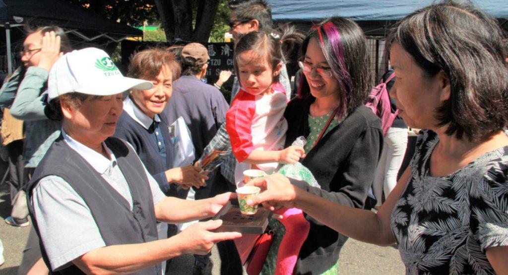 志工胡招鳳(左)奉茶給民眾。攝影/張立甲