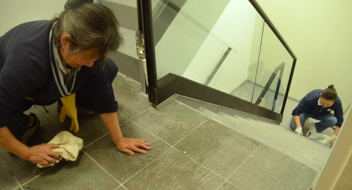 志工彎腰擦拭每片地磚。攝影/翁秀春