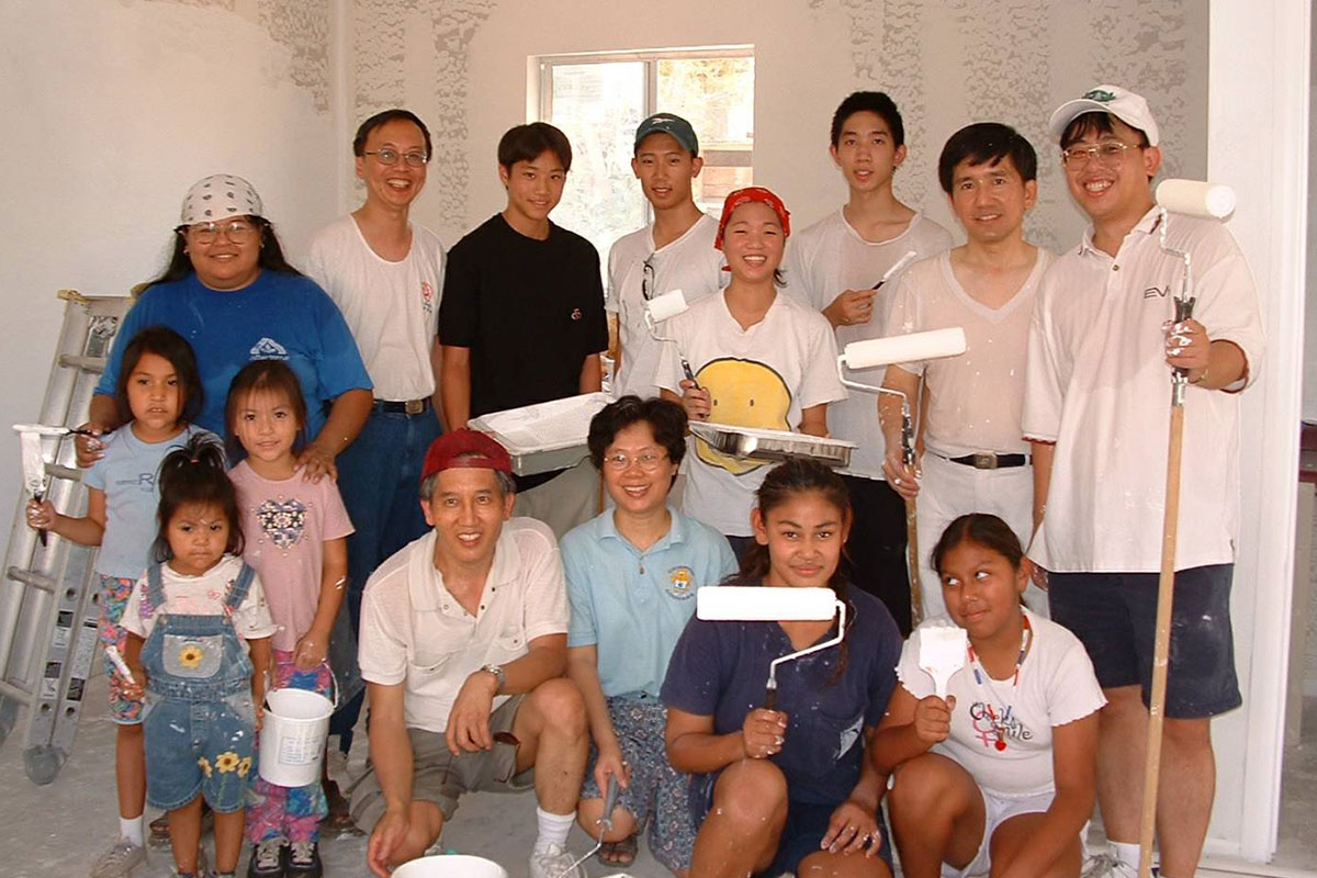Volunteers, young and old, join in to paint the house.