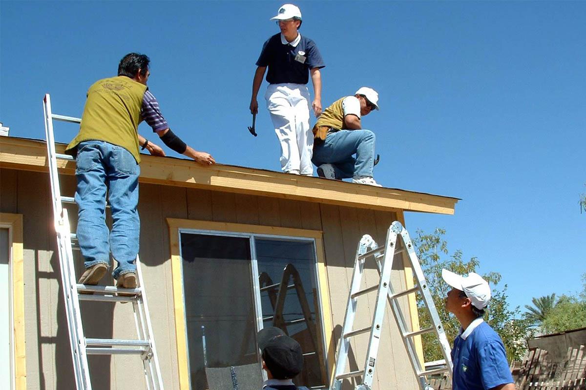 Volunteers work on the construction of the house under the blazing Arizona sun.
