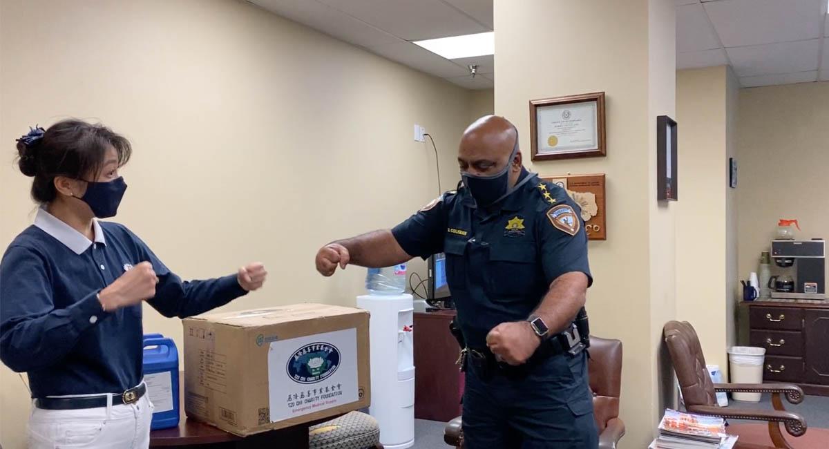 刑事司法部門指揮官達里爾(右)和志工熱情的擊拳打招呼。攝影/劉本琦